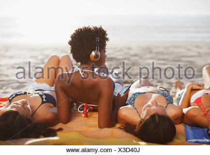 Women sunbathing together on beach - Stock Photo