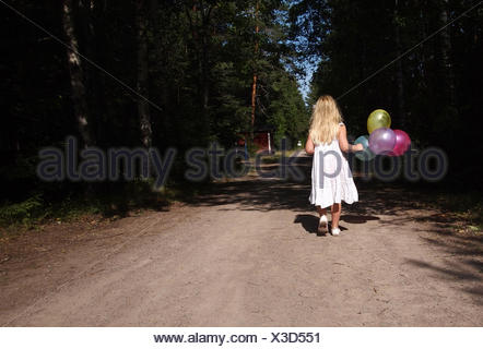 Girl walking down the road carrying a bunch of balloons, Sweden - Stock Photo