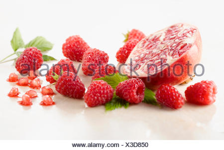 Raspberry, Rubus idaeus cultivar and Pomegranate, Punica cultivar cut in half surrounded with several raspberries and leaves on white marble. Selective focus. - Stock Photo