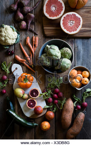 Fruit and vegetables laid out on a farm table. Carrots, cauliflowers, beets, peaches, oranges. - Stock Photo
