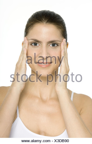 Woman holding face in hands, smiling at camera, portrait - Stock Photo