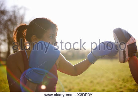 Mature woman boxer training in field - Stock Photo