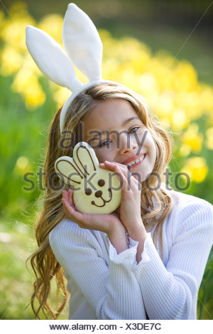 A young girl holding a chocolate bunny, wearing bunny ears - Stock Photo