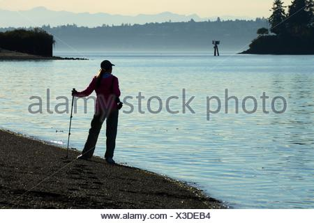 Hiker on beach at Eagle Harbor, Pritchard Park, Bainbridge Island, Washington. - Stock Photo