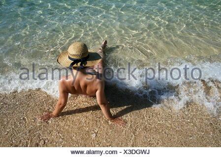 Rear view of a woman sitting in the surf, Krk Island, Stara Baska, Croatia - Stock Photo