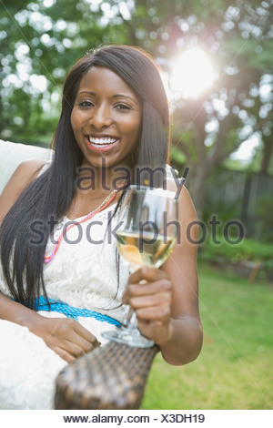 Portrait of happy woman with wineglass sitting in yard - Stock Photo