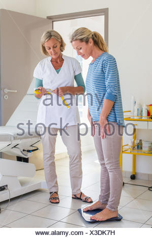 Female patient on weighing scales. - Stock Photo