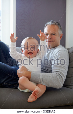 Father and baby relaxing on sofa - Stock Photo