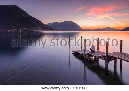 A girl on the pier of Sulzano during a winter sunset, Brescia Province, Iseo Lake, Lombardy, Italy. - Stock Photo