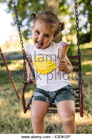 Portrait of little girl with outstretched tongue sitting on a swing eating ice cream - Stock Photo