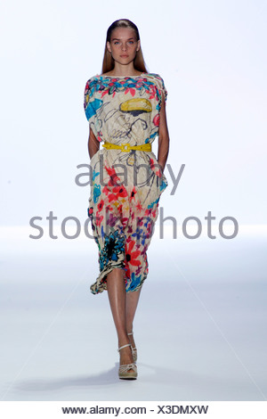 Anne Klein New York Ready to Wear Spring Summer Model long blonde hair wearing printed dress slash neck and sleeves, yellow - Stock Photo