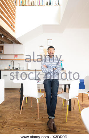 Portrait of cool young businessman in office kitchen - Stock Photo
