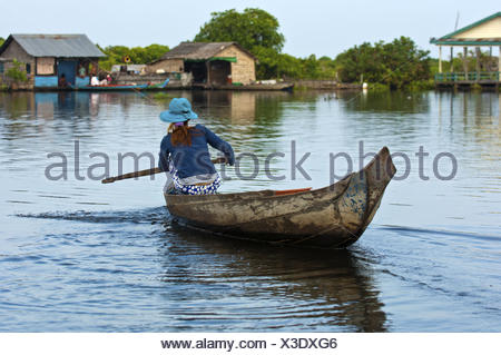 Woman paddling in a boat on the Tonle Sap lake - Stock Photo