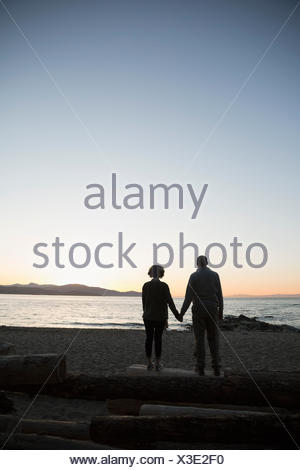 Silhouette affectionate couple on beach holding hands looking at sunset ocean view - Stock Photo