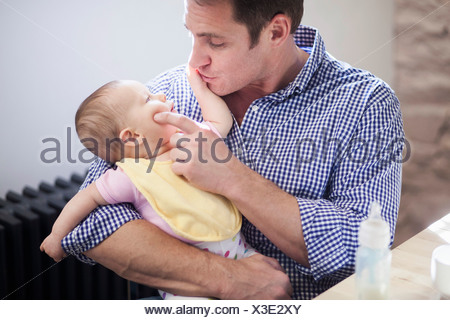 Father cradling baby daughter - Stock Photo