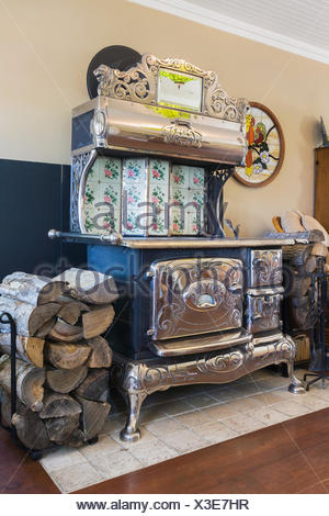 Antique black cast iron and chrome Royal wood burning cook stove in the family room inside an old reconstructed 1886 Canadiana cottage style residential home, Quebec, Canada - Stock Photo