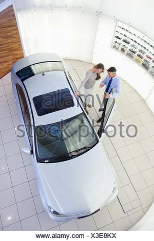 Salesman and customer looking inside car in car dealership showroom - Stock Photo