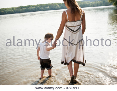 Mother guiding child in river - Stock Photo