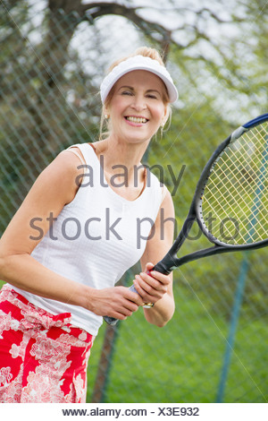 Portrait of mature woman playing tennis - Stock Photo