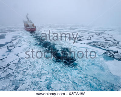 High angle view of the Canadian Coast Guard icebreaker, Pierre Radison, breaking ice. - Stock Photo