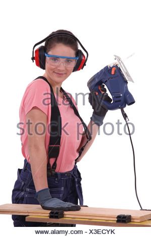 Woman using an electric saw - Stock Photo