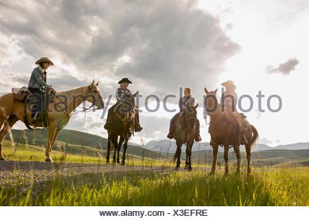 Female ranchers talking on horseback sunny road - Stock Photo
