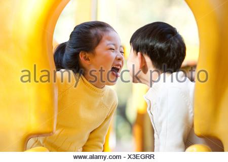 Children playing on playground slide - Stock Photo