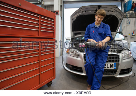 Female mechanic with diagnostic computer by open bonnet of car - Stock Photo