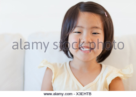 Portrait of a  cute young girl smiling as she sits on the couch - Stock Photo