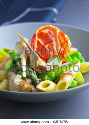 Pennes with broad beans,artichokes,asparagus and pancetta - Stock Photo
