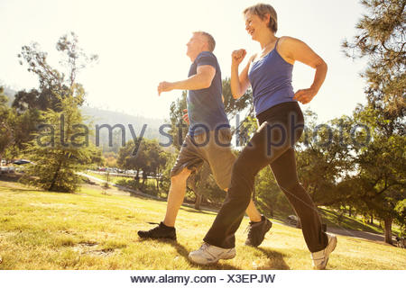 Mature couple power walking in park - Stock Photo