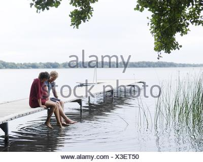 Couple sitting on pier side by side dipping toes in water, Copenhagen, Denmark - Stock Photo
