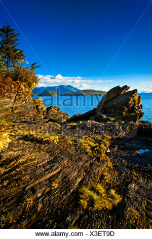 Sunlit rocks line the blue waters of Settler's Cove,  Settler's Cove State Recreation Site, Ketchikan, Southeast Alaska, Summer - Stock Photo