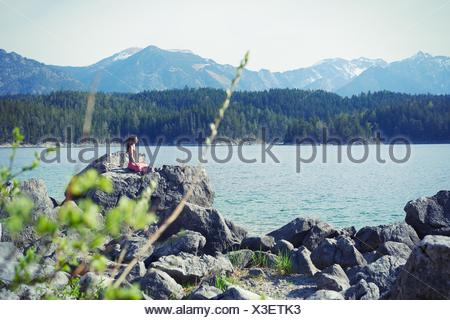 Mid adult woman, sitting on rock, in yoga position - Stock Photo
