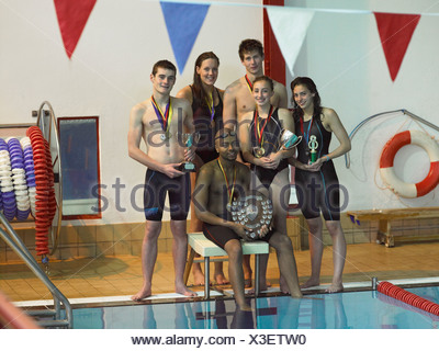 Swimmers holding trophies at pool - Stock Photo
