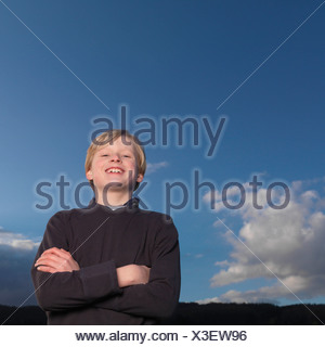 Boy standing with arms crossed,  smiling