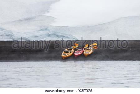 Three Kayaks lined up on the volcanic beach of Whalers Bay become the centre of interest in a simple design, Deception Island, South Shetland Islands - Stock Photo
