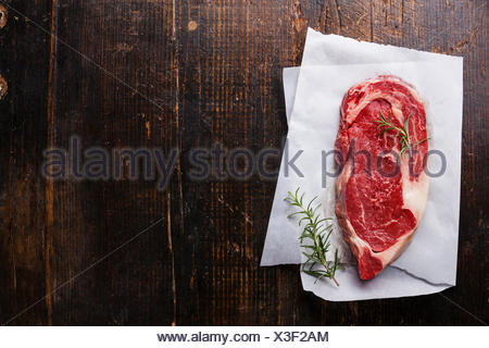 Raw fresh marbled meat Black Angus Steak and rosemary on dark wooden background - Stock Photo