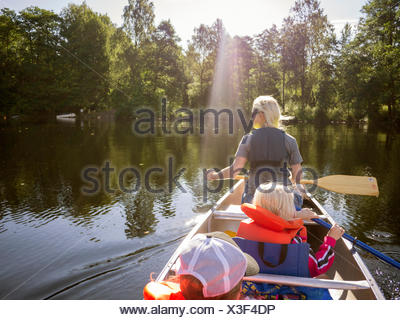 Mother, son (8-9) and daughter (6-7) navigating across lake in rowboat - Stock Photo