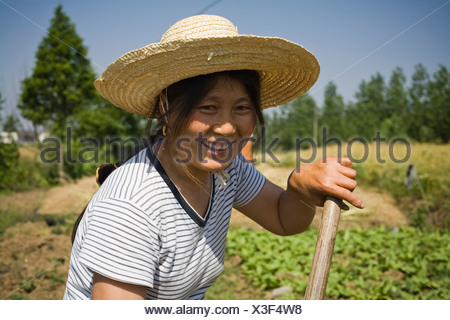 Woman with straw hat working in field outdoors - Stock Photo