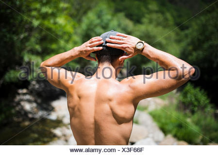 Back of shirtless young man wearing wrist watch - Stock Photo