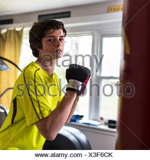 Teenage boy wearing boxing gloves - Stock Photo