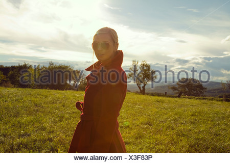 Young woman in field posing in sunglasses - Stock Photo