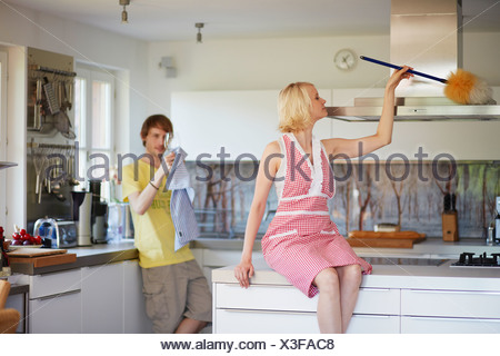 Couple cleaning together in kitchen - Stock Photo