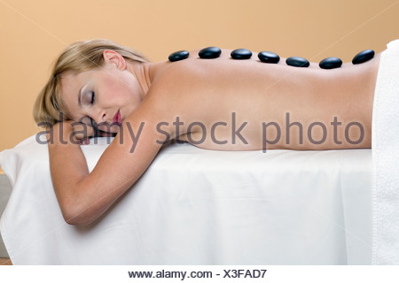 Young woman relaxing while having lastone therapy treatment, eyes closed - Stock Photo