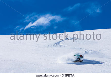 Professional Snowboarder and 2014 Olympic Gold Medalist, Jamie Anderson, rides fresh powder on a sunny day while snowboarding in Haines, Alaska. - Stock Photo