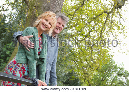 Portrait of smiling adult couple in park - Stock Photo