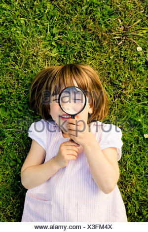 Little girl lying on a meadow looking through magnifying glass - Stock Photo