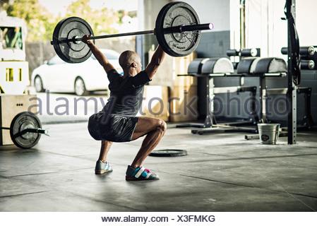 Young man lifting barbells in gymnasium - Stock Photo