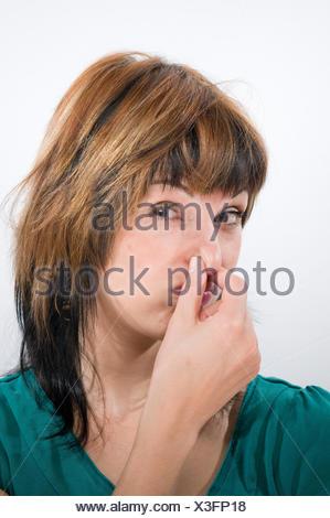 Kopf-und-Schulter-Aufnahme einer jungen Frau mit Blick in die Kamera sich die Nase zuhaltend - Stock Photo